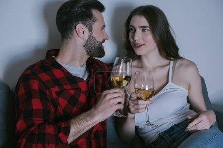 Photo pour Heureux jeune couple assis sur canapé, se regardant tout en tenant des verres de vin blanc - image libre de droit