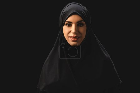 Photo pour Belle femme musulmane souriant à la caméra isolée sur noir - image libre de droit