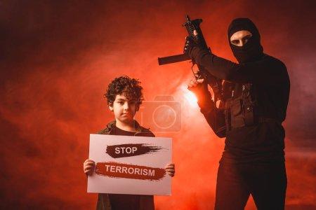 Foto de Terrorista en pasamontañas sosteniendo ametralladora cerca de niño musulmán con letras de stop terrorism en tarjeta sobre fondo negro con humo rojo - Imagen libre de derechos