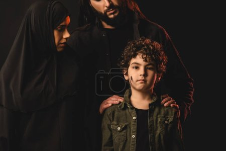 Photo for Muslim parents hugging son with messy face isolated on black - Royalty Free Image