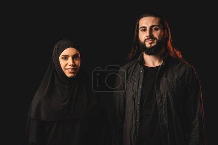 Photo pour Sourire musulman couple regarder caméra isolé sur noir - image libre de droit