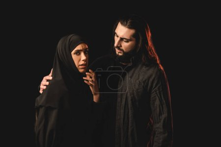 Photo for Muslim man embracing worried wife isolated on black - Royalty Free Image