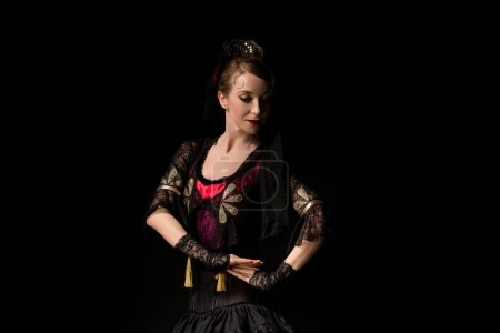 Photo pour Attrayant danseur en robe dansant flamenco isolé sur noir - image libre de droit