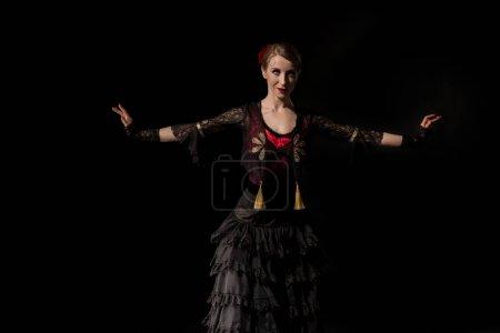 Photo pour Jolie femme avec les mains tendues dansant flamenco isolé sur noir - image libre de droit
