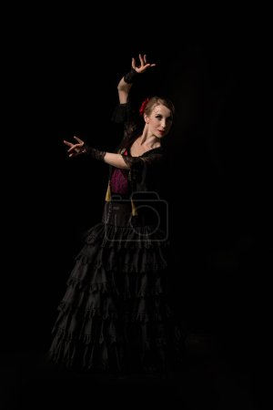 Photo for Pretty flamenco dancer in dress dancing isolated on black - Royalty Free Image