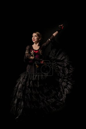 Photo pour Danseuse de flamenco joyeuse en robe tenant des castagnettes et dansant isolée sur noir - image libre de droit