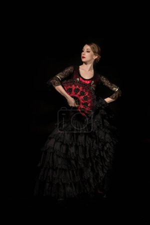 Photo for Elegant dancer with fan dancing flamenco isolated on black - Royalty Free Image