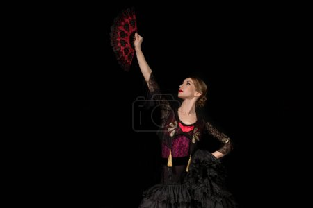 Photo for Beautiful dancer looking at fan while dancing flamenco isolated on black - Royalty Free Image