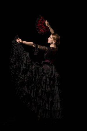 Photo pour Belle jeune danseuse tenant ventilateur tout en dansant flamenco isolé sur noir - image libre de droit