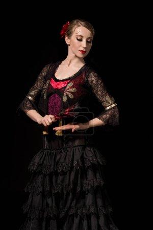 Photo pour Jeune danseur tenant un ventilateur tout en dansant le flamenco isolé sur noir - image libre de droit