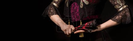 horizontal image of young flamenco dancer holding fan isolated on black