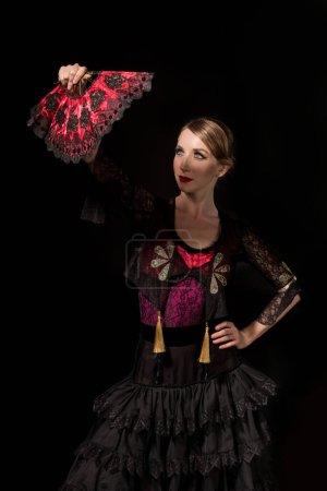 jolie danseuse de flamenco debout avec la main sur la hanche et regardant ventilateur isolé sur noir