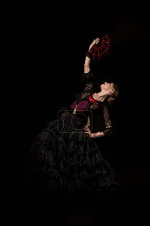 pretty flamenco dancer with hand on hip holding fan and dancing isolated on black