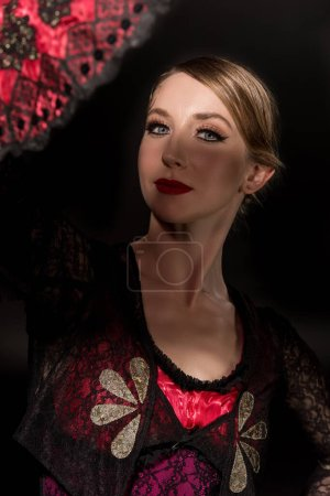 Photo for Selective focus of pretty flamenco dancer looking at camera near fan isolated on black - Royalty Free Image