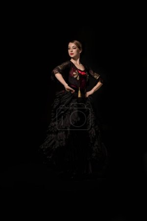 Photo for Elegant and beautiful flamenco dancer with hands on hips isolated on black - Royalty Free Image