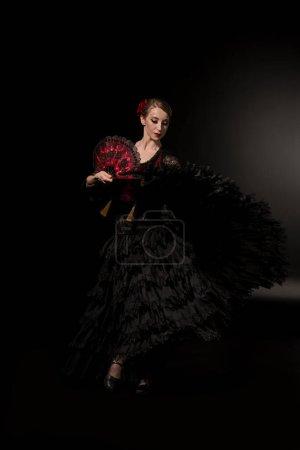 Photo pour Jeune danseuse de flamenco tenant ventilateur et dansant sur noir - image libre de droit