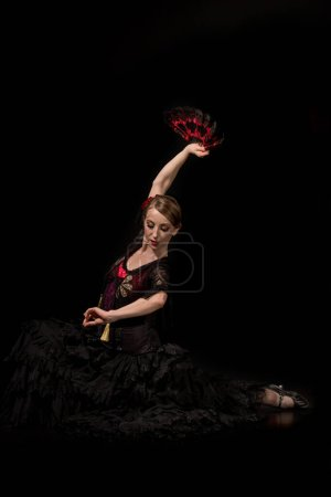 Photo pour Élégante danseuse de flamenco tenant le ventilateur au-dessus de la tête et assise sur le noir - image libre de droit