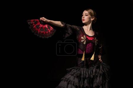 Photo pour Élégante femme tenant ventilateur et dansant flamenco isolé sur noir - image libre de droit