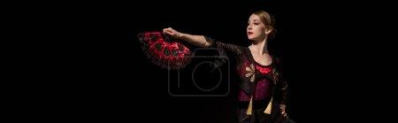 Photo pour Récolte horizontale de femme élégante tenant ventilateur et dansant flamenco isolé sur noir - image libre de droit