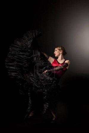 Photo pour Joyeuse et jeune danseuse de flamenco en robe dansant sur noir - image libre de droit