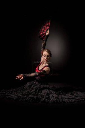 Photo pour Jeune danseuse de flamenco tenant le ventilateur au-dessus de la tête tout en étant assise sur noir - image libre de droit