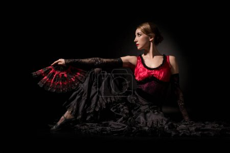 Photo pour Élégant danseur de flamenco tenant ventilateur et assis sur noir - image libre de droit