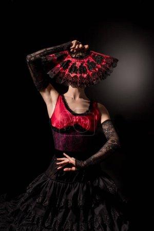 Photo pour Jeune danseuse de flamenco couvrant le visage avec ventilateur sur noir - image libre de droit