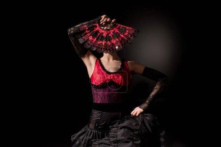 Photo pour Jeune danseuse de flamenco en robe couvrant le visage avec ventilateur sur noir - image libre de droit