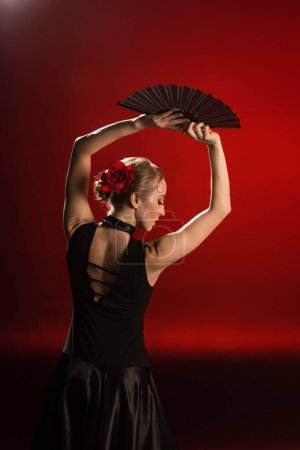 Photo for Young flamenco dancer in dress holding fan above head on red - Royalty Free Image