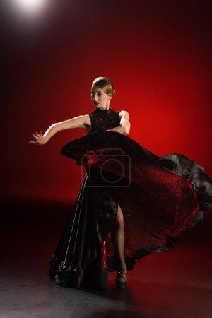Photo pour Jolie robe touchante danseuse de flamenco tout en dansant sur rouge - image libre de droit