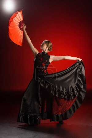Photo pour Élégante danseuse de flamenco en robe tenant ventilateur tout en dansant sur rouge - image libre de droit