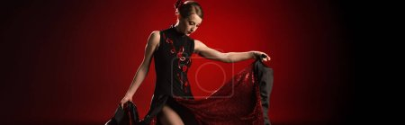panoramic concept of young and pretty woman touching dress while dancing flamenco on red