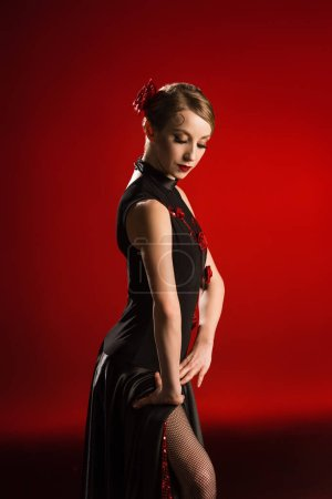 attractive and young dancer in dress dancing flamenco on red