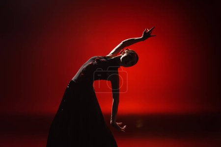 Photo for Silhouette of young and attractive woman dancing flamenco on red - Royalty Free Image
