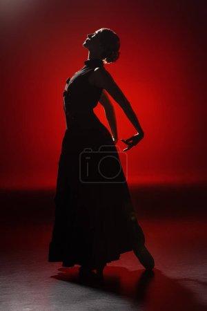 Photo pour Silhouette de jeune femme élégante dansant le flamenco sur rouge - image libre de droit