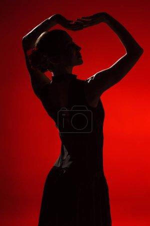 Photo pour Profil de jeune et élégante femme dansant le flamenco sur rouge - image libre de droit