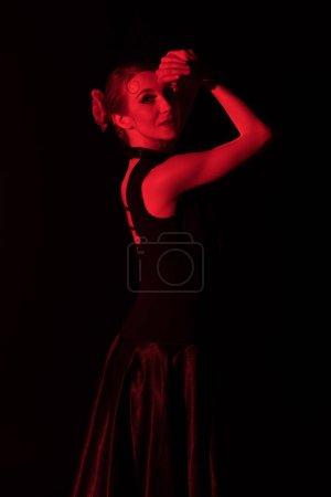Photo pour Éclairage rouge sur une jolie danseuse de flamenco en robe isolée sur noire - image libre de droit