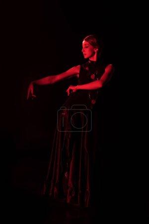 Photo pour Éclairage rouge sur danseuse de flamenco en robe dansante isolée sur noir - image libre de droit
