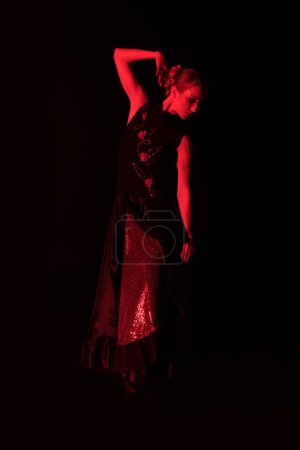 Photo for Red lighting on pretty woman dancing flamenco isolated on black - Royalty Free Image