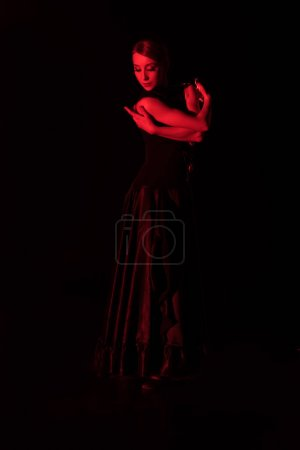Photo for Red lighting on elegant woman dancing flamenco isolated on black - Royalty Free Image