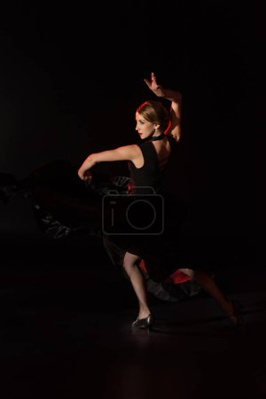 Photo for Pretty young dancer dancing flamenco on black - Royalty Free Image