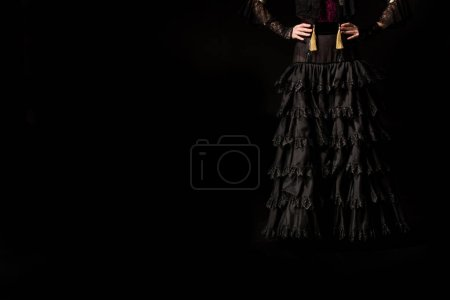 Photo for Cropped view of young flamenco dancer standing with hands on hips isolated on black - Royalty Free Image