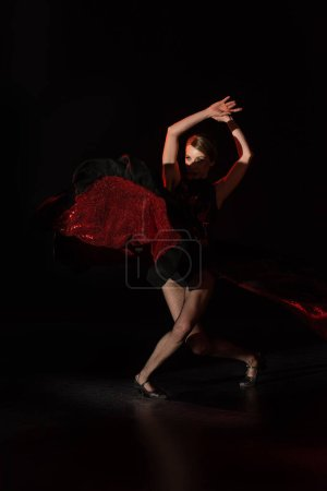 pretty young dancer with hands above head dancing flamenco on black