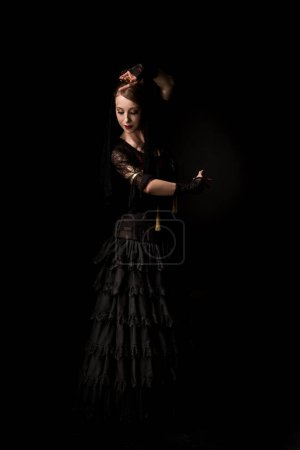 pretty young flamenco dancer dancing in dress isolated on black