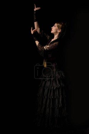 Photo pour Vue de côté de jolie danseuse flamenco dansant isolée sur noir - image libre de droit