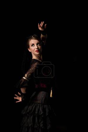 Photo pour Élégante danseuse de flamenco regardant loin et dansant isolée sur noir - image libre de droit
