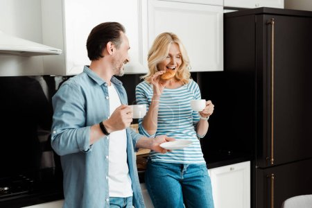 Lächelnder Mann mit Kaffeetasse und Blick auf Frau, die in Küche Croissant isst