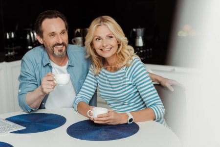 Photo for Selective focus of positive mature couple smiling away while drinking coffee in kitchen - Royalty Free Image