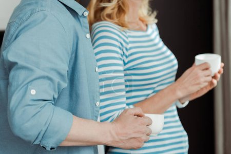 Cropped view of man holding cup of coffee near wife at home