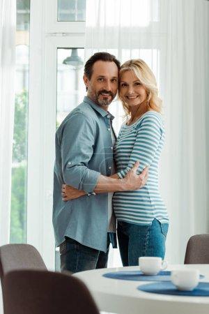 Photo pour Vue latérale du couple mature étreignant et souriant à la caméra près des tasses à café sur la table de cuisine - image libre de droit